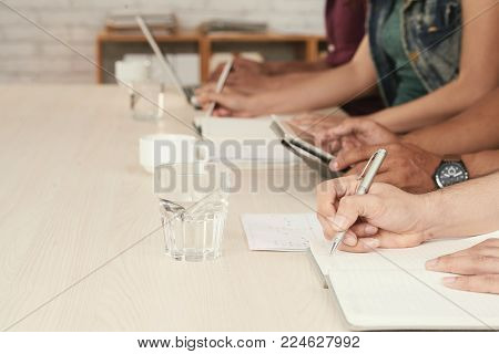 Hands of business people taking notes when attending conference