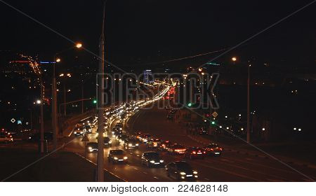 Road and cars with glowing headlight on background evening street. Intense vehicular traffic. Rapid night life of city.