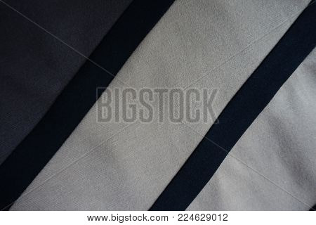 Two black ribbons sewn to grey and beige fabric