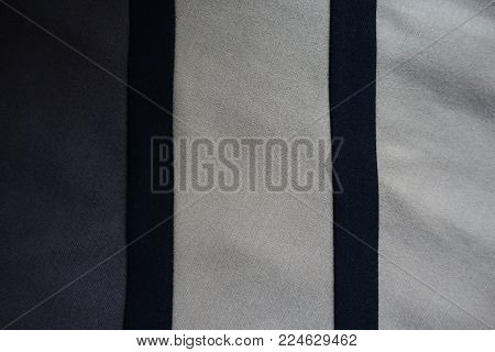 Pair of vertical black ribbons sewn to grey and beige fabric
