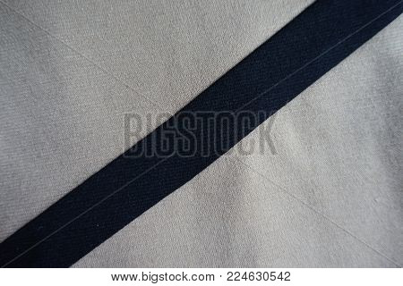 Diagonal black ribbon sewn to light grey fabric
