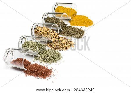 glass jars with various spices on white background