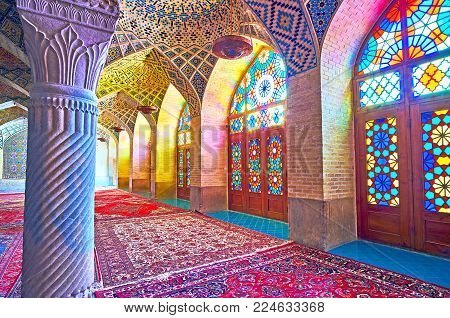 SHIRAZ, IRAN - OCTOBER 12, 2017: The scenic stained glass windows in Nasir Ol-Molk mosque provide the colored lights to the prayer hall, on October 12 in Shiraz.