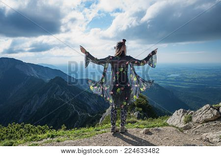 Young Woman With Fluttering Cape, Enjoying Lookout From Herzogstand Mountain To Alpine Foothills.