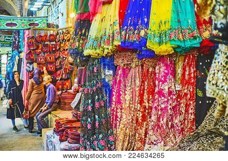 SHIRAZ, IRAN - OCTOBER 12, 2017: The showcase of the textile store in Vakil Bazaar with bright colored synthetic materials (organza, etc), decorated with prints and embroideries, on October 12 in Shiraz.
