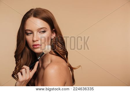 Beauty portrait of calm ginger woman with long hair posing sideways while looking back and holding cosmetics brush over cream background
