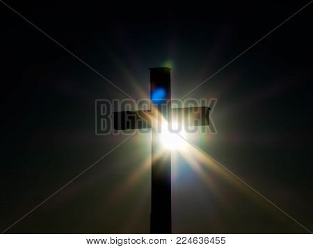 Sunset behind silhouette  catholic cross on a cold winter day, visible lens flare.