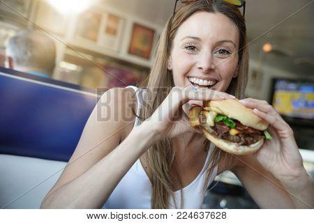 Portrait of cheerful girl eating hamburger in fast food restaurant