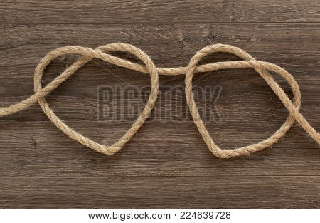Two heart ropes connected to a knot on an old wood