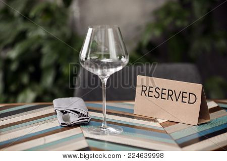 Reserved table with empty glass and cutlery in the cafe