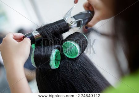Professional hairdresser makes hairstyle girl create curls with curling iron beauty salon.