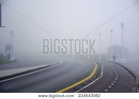 Photo of a road with fog and several Street lights