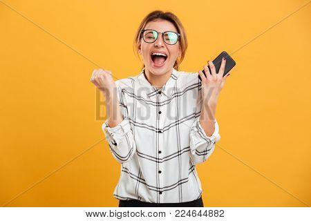 Portrait of ecstatic woman wearing eyeglasses clenching fist like winner while holding smartphone in hand isolated over yellow background