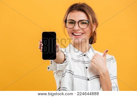 Portrait of beautiful flurry woman showing on camera black screen of mobile phone and gesturing thumb up isolated over yellow background