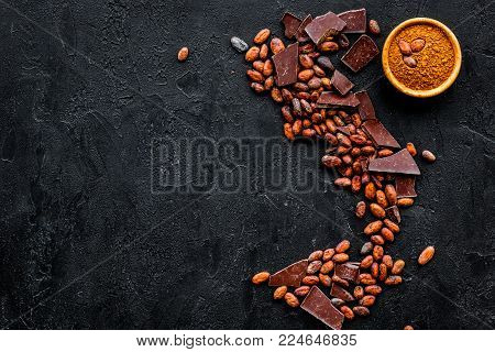 Chocolate and cacao concept. Cocoa powder in bowl near cocoa beans and broken chocolate on black background top view.