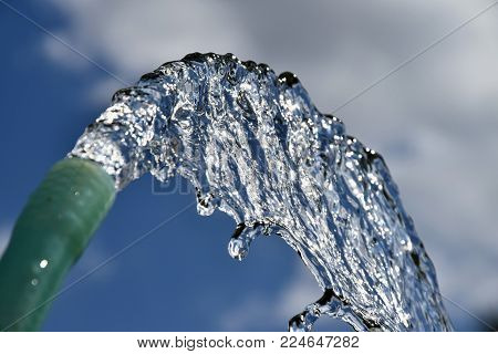 Water flows from the garden hose. Wasteful wasting water. Global warming shortage of water.