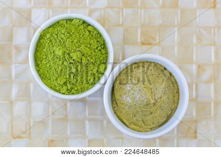 Fine Ground Japanese Matcha green tea leaves powder next to Green tea scrub with walnut shell and Cocoa exfoliator, top view