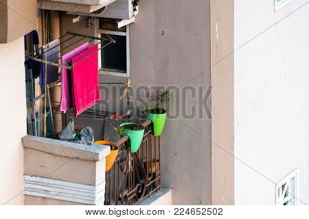Cramped and crowded small apartment balcony with clothes drying hanger, flower plants and other odds and ends. Shows how most people have to live due to the expanding population