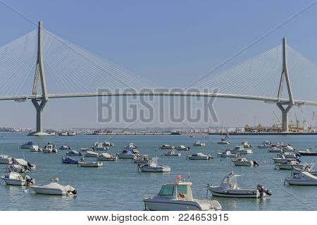horizontal view of boats at cadiz harbor with the bridge of the constitution of 1812 in the background