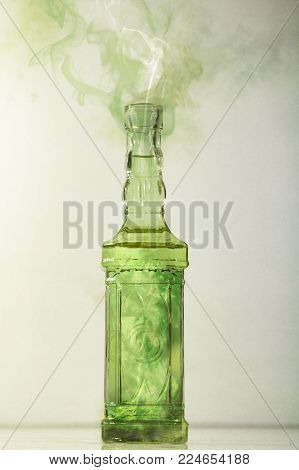 Magic potion releasing cloud of smoke or fumes, green potion in a translucent bottle