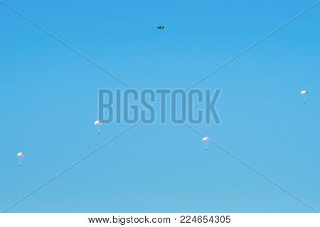 Airborne Troops A Mass Parachute Drop Over The Sea. On A Blue Sky Background.