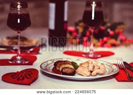 Close up table served for romantic dinner for two with glasses of red wine, roasted chicken fillet with vegetables on plate, red heart and flowers