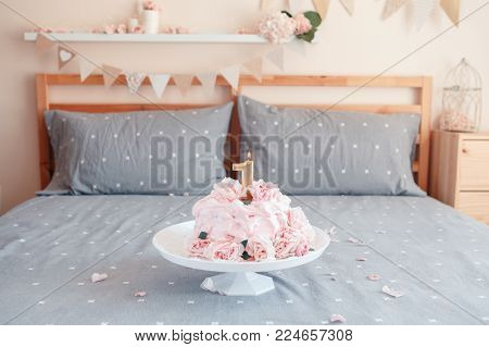 Gourmet pink cake with large natural real rose flowers and candle on stand in bedroom for baby birthday. Home indoors cake-smash first year concept
