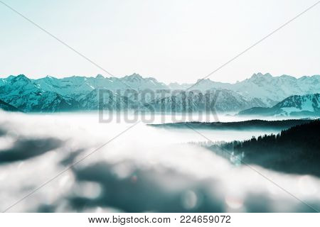 Cold blue toned winter landscape with low lying clouds or mist in the valleys and distant snowy alpine mountain peaks