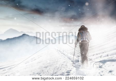 Extreme sport enthusiast hiking through a snow blizzard in winter along a mountain footpath in high altitude mountainous terrain in a concept of fitness and active lifestyle