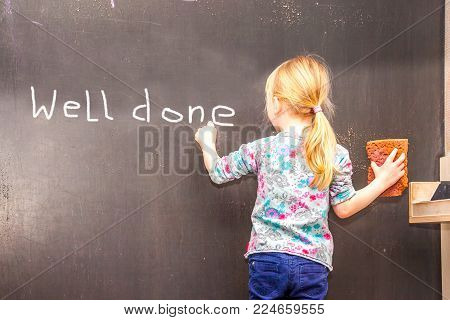 Cute little girl writing Well done on chalkboard in a classroom
