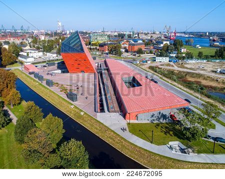 Gdansk, Poland - September 30, 2017: Aerial view of the Museum of the Second World War. Gdansk skyline on sunny morning with harbor, shipyard, cranes and ships in the background
