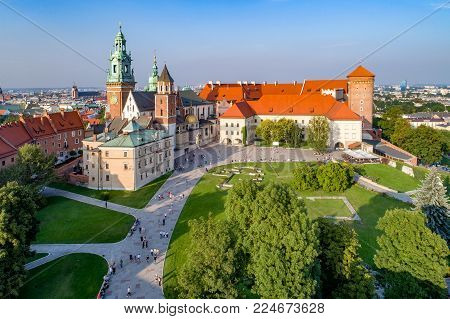 Royal Wawel Gothic Cathedral in Cracow, Poland, with Renaissance Sigmund Chapel with golden dome, part of Wawel Castle, yard, park and tourists. Aerial view in sunset light