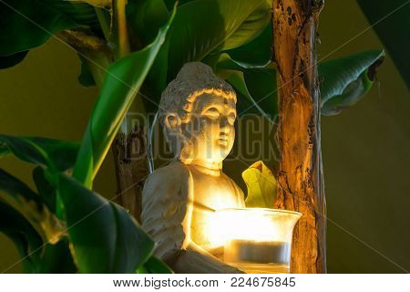 Sitting Buddha surrounded by banana trees hold the burning candle in hands