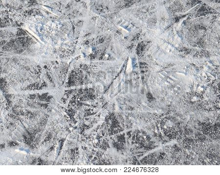 Surface of the outdoor skating rink marked with traces of skates and replete snow
