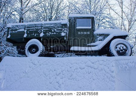 old green truck covered with snow on pedestal