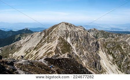 panorama of Western Tatras mountains with nearest Pachola peak and many other peaks from Banikoc peak in Slovakia during nice summer day with blue sky