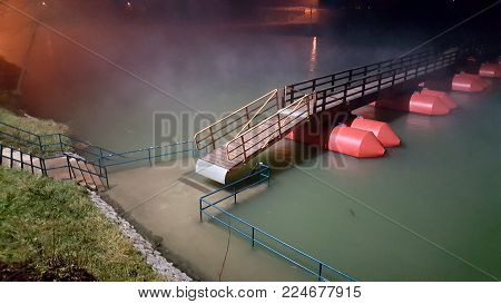 Wooden pontoon bridge surrounded with fog at night during flood, held only by ankers and completely risen from concrete pier