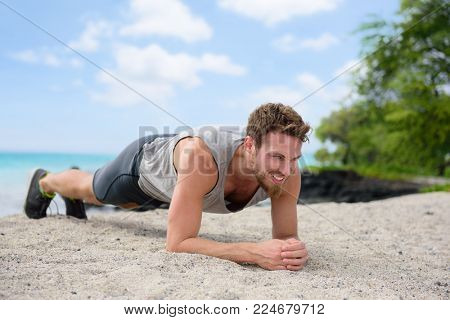 Fitness man planking doing plank exercise on beach. Summer workout for toned abs fit body. Young men lifestyle.