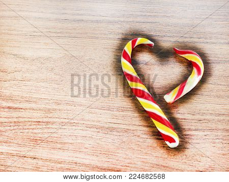candy in the shape of heart on a wooden background for the celebration of Valentine's Day. Heart is broken. Cheating.