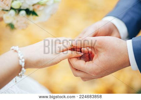 The groom wears a gold ring to the bride at the wedding ceremony. Wedding in autumn