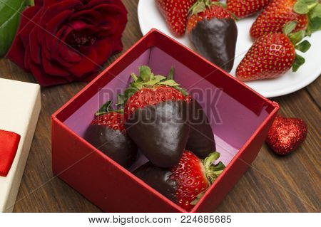 Box with tasty chocolate dipped strawberries and bouquet of flowers on table.