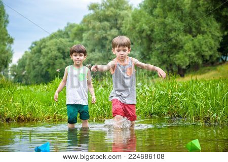 Two Little Brothers Playing With Paper Boats By A River On Warm And Sunny Summer Day.