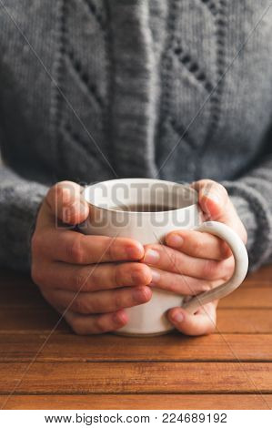 Woman sat at table with mug of tea wearing cozy gray cardigan