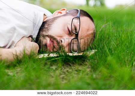 weary man relaxing outdoors lying on the grass with a book