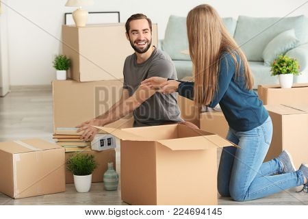 Young couple packing moving boxes in room