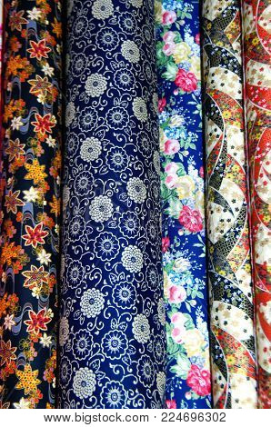 Variety of colorful fabric clothes at street bazaar.