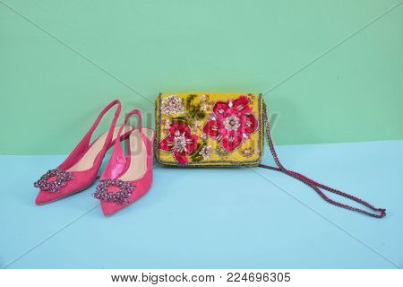 Embroidered hand made flowers handbag with red shoes.- blue and green  background