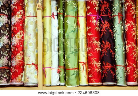 Variety of colorful floral fabric on hanging in store