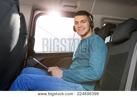 Man listening to audiobook through headphones in car