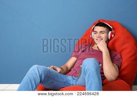 Man listening to audiobook through headphones near color wall